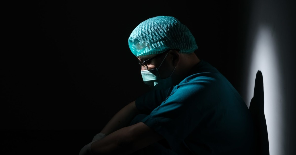 doctor sitting in the dark. mood is depressed.