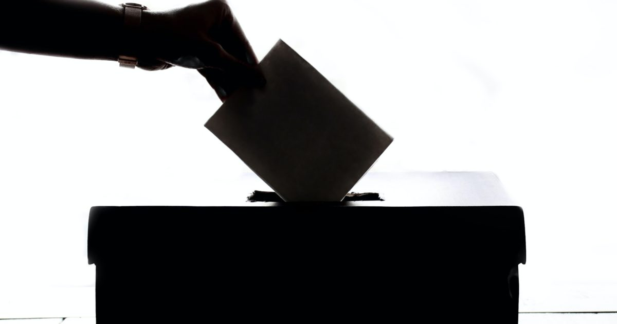silhouette of a voter voting by putting their ballot in the a ballot box